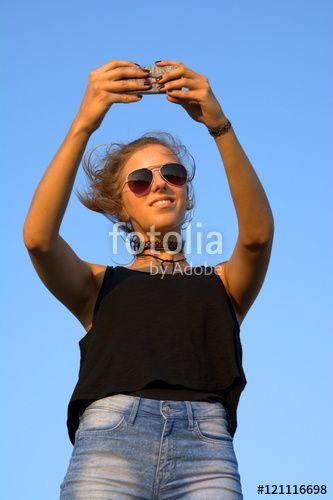 Attraktive junge Frau mit Sonnenbrille macht ein Selfie vor blauem Himmel im Sommer, Sonne, Smartphone, Handy, Selbstportrait - Fotolia - © SULUPRESS / Torsten Sukrow