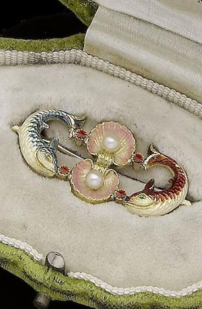 An Art Nouveau enamel and pearl brooch, by Alfred Phillips, circa 1895. The two pink enamel scallop shells, each centred with a 3.2mm pearl, between two leaping fish set with blue, red and white enamel, maker's mark AP.: