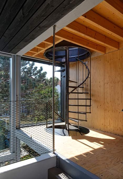 A traditional townhouse overhauled by adding mezzanine floors, a glass elevation, a triple-height kitchen and a spiral staircase.