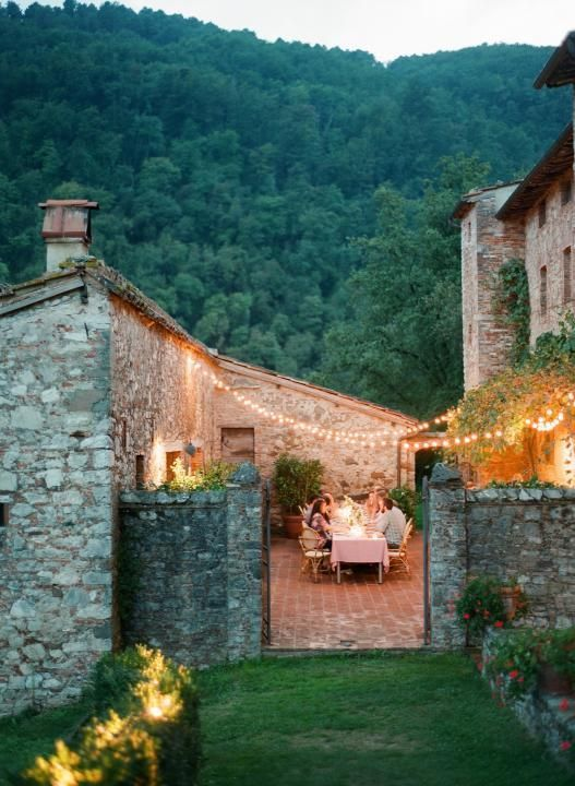 Outdoor dining in courtyard. European Farmhouse and French Country Decorating Style Photos. #outdoordining #farmhouse #exterior #europeanfarmhouse