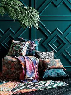 colorful pillow pile against teal green wall, teal blue, jade, blue-green, green-blue, pantone shaded spruce