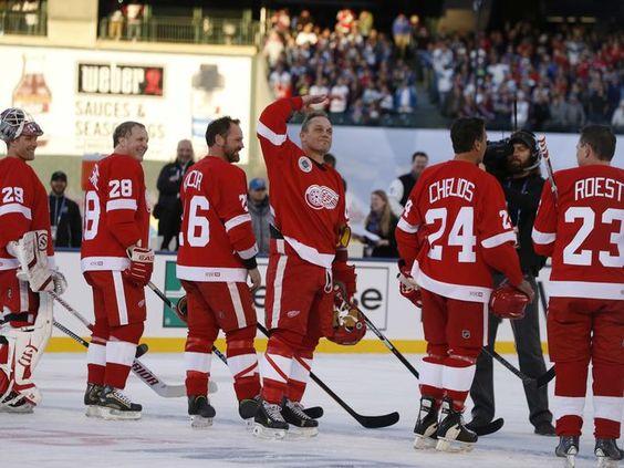 Detroit Red Wings alumnus Darren McCarty, center, salutes
