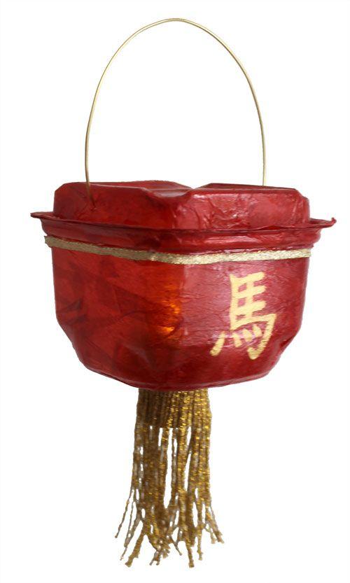 Lanterne chinoise faite de papier de soie collé sur un récipient de petites tomates cerises.  Une chandelle LED éclaire la lanterne dans le noir.
