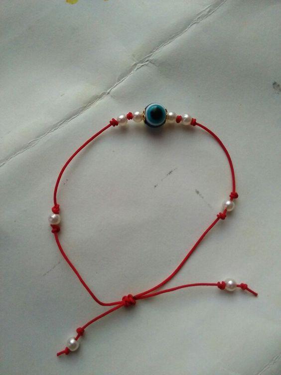 Pulsera o manilla ojo turco. Hilo rojo, perlas blancas y nudo básico.