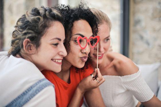 tres chicas jóvenesprobablemente posando para hacerse un selfie, la del medio lleva a modo de máscara de carnaval unas gafas falsas d corazones sujetas con un palito