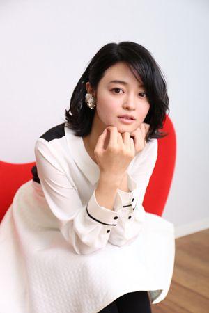 白いワンピースを着て赤いソファーに座っている小林涼子の画像