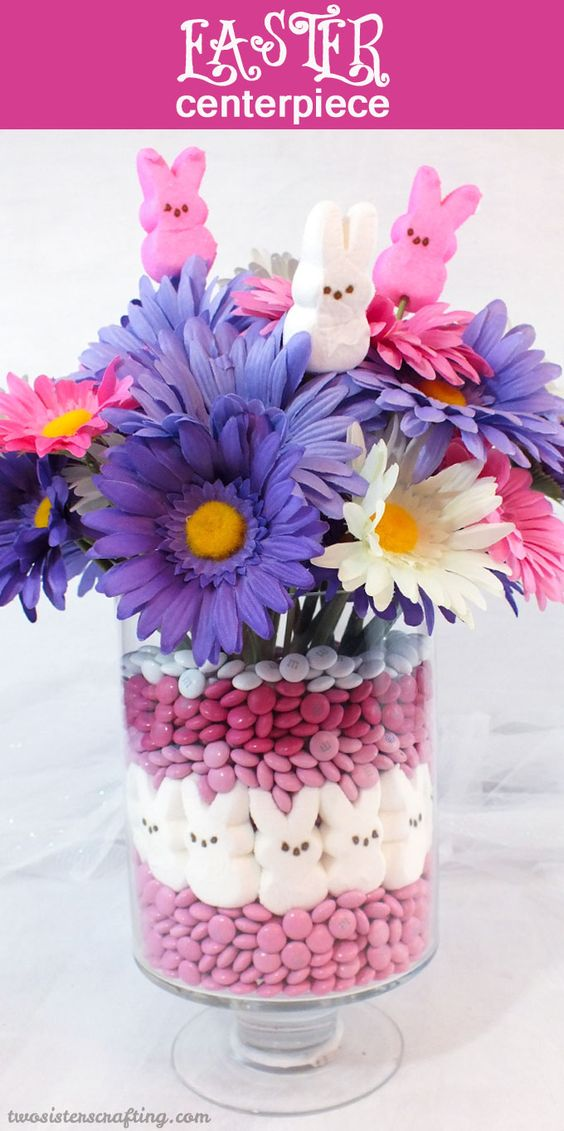 This adorable Easter Centerpiece will be everyone's favorite Easter decoration - so fun and so easy to make. All you need are M&M's, Peeps and some flowers to make this cute Easter Craft.  For more fun Easter ideas, follow us at https://www.pinterest.com/2SistersCraft/: