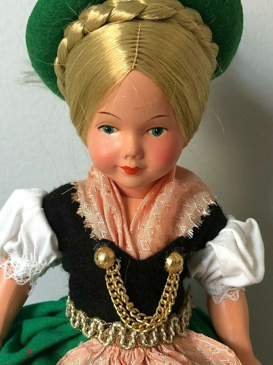 "Doll Rosel is made by German Company Schmider. She is 9"" tall Celluloid doll in traditional Bavarian costume. Rosel is in a good condition; some missing pain to one of her legs (see photo). Comes in original clear plastic box/case with handle. No tag.Whether you have lots of passion for dolls or you are a doll collector we invite you to visit our newly launched website - www.dollkingdomus.com.This is a place to explore the world of dolls and connect with other doll collectors. We are very excite"