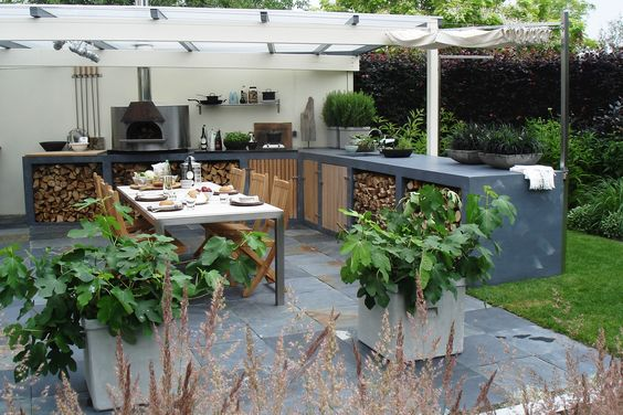 Outdoor pizza oven and sink with cupboards underneath, fig trees in tubs and…