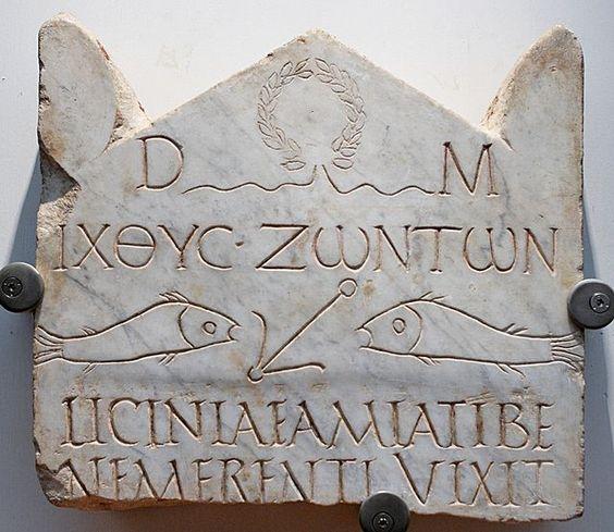 """Esta estela funerária do século III está entre as mais antigas inscrições cristãs, escrita simultâneamente em grego e latim. A abreviatura """"D.M."""" no topo refere-se a Di Manes, os espíritos tradicionais romanos da morte, mas é acompanhada pelo símbolo cristão"""