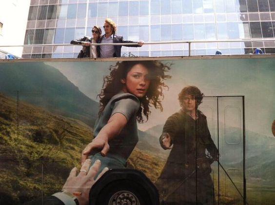 Cait & Sam on a bus advertising Outlander season 1