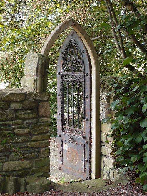 Garden gate ideas ad inspiration: gothic arch door flanked by stone walls in a lush green garden. #european #gardengate #gothic #gardendecor