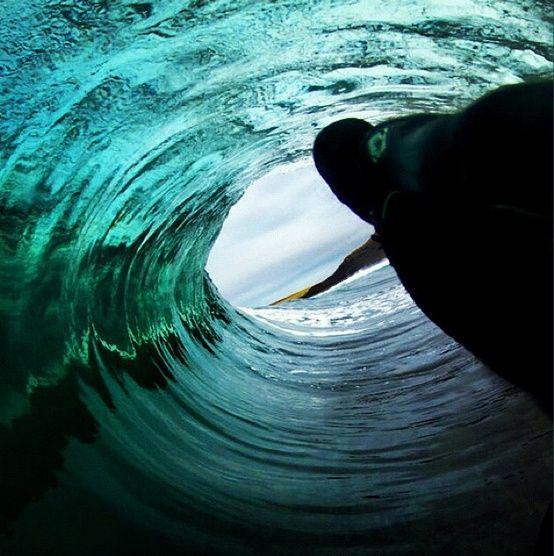 波のトンネルとサーファー