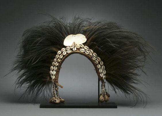 Papua New Guinea | New Guinea headdress of classical form, with cowrie shell headband, a large ovoid shell apex, and strings of seeds and shells to either side; the whole crowned with a dense spread of black cassowary feathers | Est. 2,500 - 3,500$: