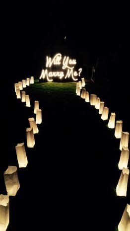 "11 Creative Engagement Announcement Photo Ideas With Signage: This candlelit proposal is gorgeous. We love the winding path leading to the luminous ""Will You Marry Me?"" sign {Photo courtesy of @sarah}"
