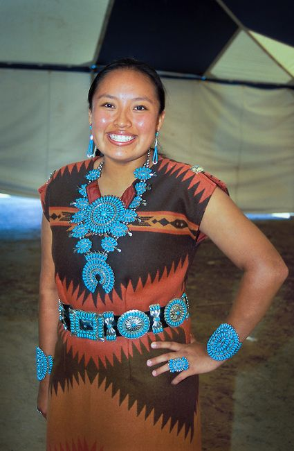 Navajo woman dressed in a woven wool dress adorned with traditional turquoise necklace, braclets, concho belt and ring attends the annual Shiprock festival in New Mexico: