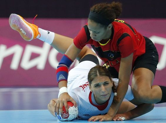 Croatia's Andrea Penezic (L) falls to the ground after being pushed by Angola's Nair Almeida in their women's handball Preliminaries Group A match at the Copper Box venue during the London 2012 Olympic Games July 30, 2012.