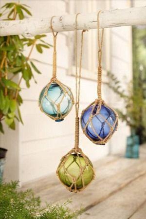 Maritime Deko. Die Kombination aus blauen Farbtönen und dem Fischernetz aus Sisal macht die Glas-Kugeln zum Hängen zu einer tollen maritimen Dekoration.