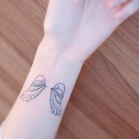 Wrist tattoo of two wings by Seoeon Tatuajes en el Antebrazo