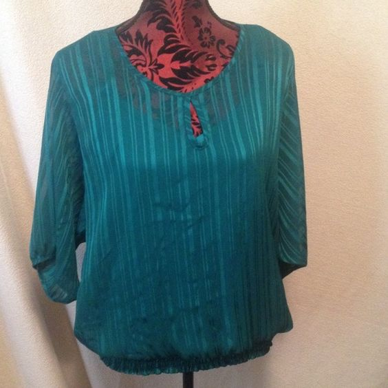 """Sheer blouse with sewn in tank. This is a great """"go-to"""" blouse. Rich green in color, great for fall; sheer top, great for the warmer weather. V-neck tank top is sewn in to the blouse and comes in at a 3"""" wide elastic waistband. Key hole opening in front. There is a small snag in the right sleeve, as pictured. Tops Tank Tops"""