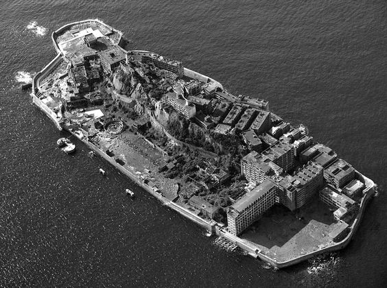 """Hashima Island, or Gunkanshima (meaning """"Battleship Island,"""" so nicknamed for it's nautical shape), was a former coal mining community established in 1887. The mine was shut down in 1974 and the city abandoned. Now it has a new nickname: Ghost Island."""