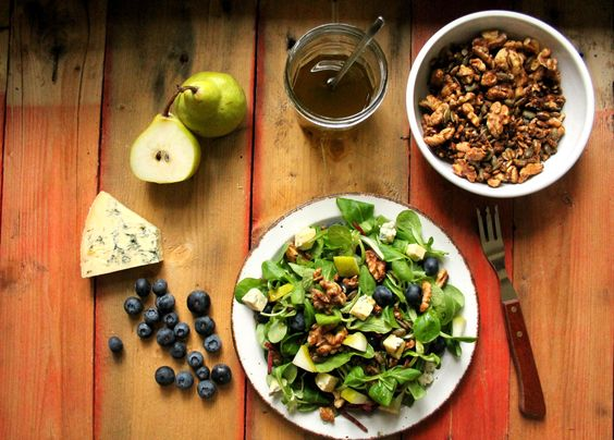 ensalada de queso azul, pera, arandanos con nueces y semillas caramelizadas