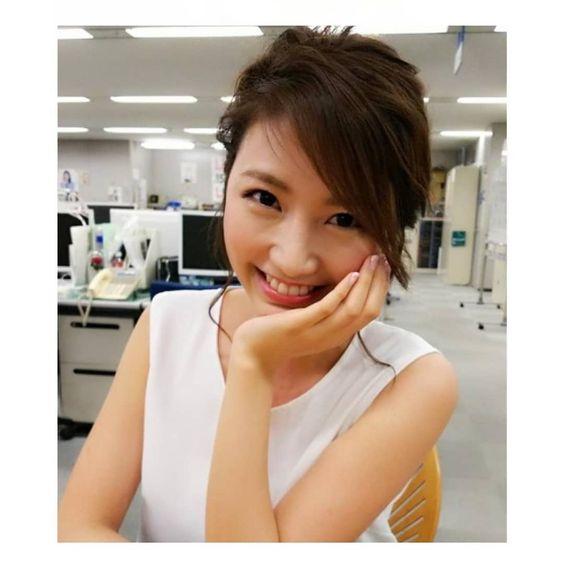 アナウンサー室のデスクでキュートな笑顔を見せる三田友梨佳アナの画像