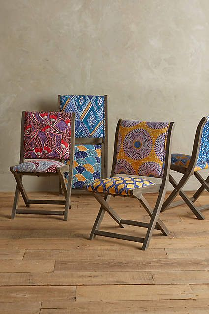 Hand-screen-printed upholstery in bright Dutch wax motifs top this folding wood-frame chair.