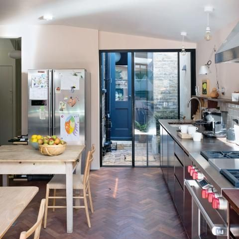 The kitchen, originally painted all white, is now a soft shade, Pink Ground by Farrow & Ball. Cabinets in phenolic plywood have reclaimed lab worktops.