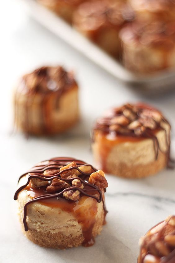 Mini Turtle Cheesecakes feature a thick graham cracker crust, vanilla cheesecake filling, and are topped with caramel, toasted pecans, and chocolate!