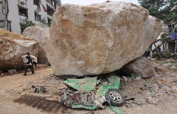 A flattened taxi lies under a boulder on the earthquake-damaged streets of Beichuan in Sichuan Province on May 16