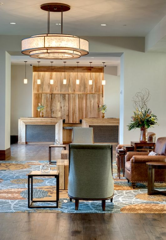 The wood reception desk is cool with the wood paneling for Cool office reception