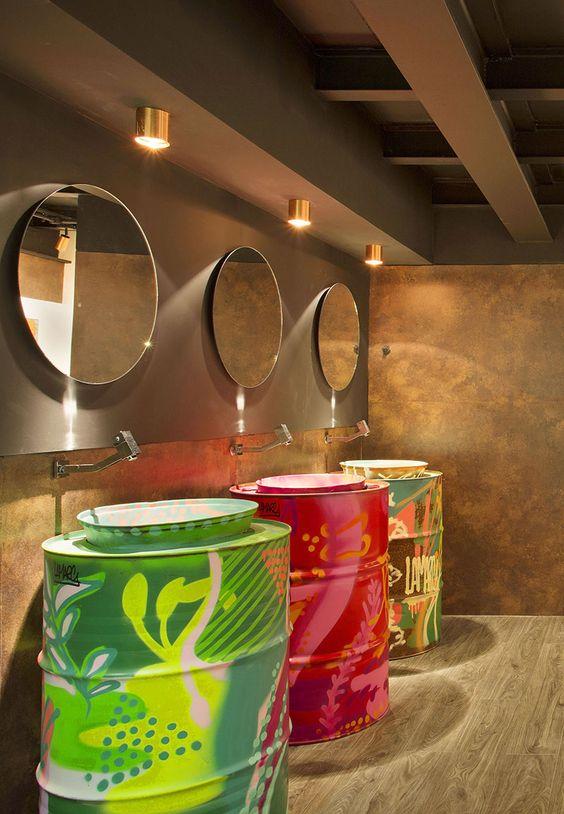 16. BANHEIRO COM ARTE FEMININO - bancadas e cubas dos lavatórios feitas a partir de tonéis de diesel grafitados