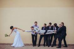 Funny wedding picture. Bride taking the groom from groomsmen