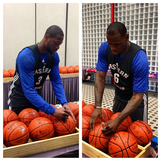 Dwayne Wade and Lebron James taking time to autograph a few basketballs
