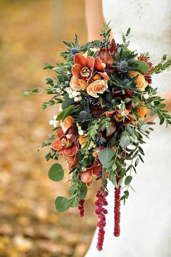 Autumn/Fall Cascade With Orange Roses, Orange Cymbidium Orchids, White Snowberry, Red Amaranthus, Blue Eryngium Thistle, Blue Privet Berries, Several Varieties Of Greenery/Foliage