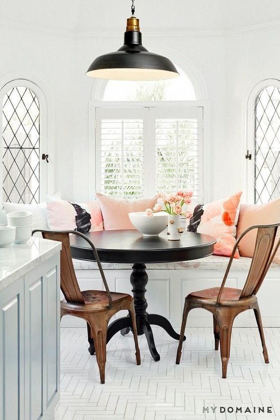 Bright dinning nook with herringbone white floors, bronze metal chairs, and a black pendant light: