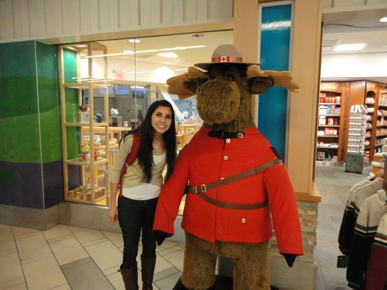 Foto com a Carol e um alce de pelucia vestido de guarda canadense em frente a uma loja no aeroporto de Vancouver
