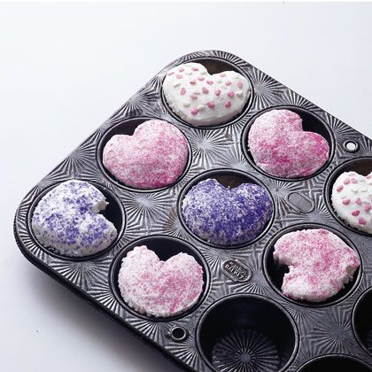 Fun heart-shaped cupcakes made by putting a marble on the side of the cupcake paper before baking.