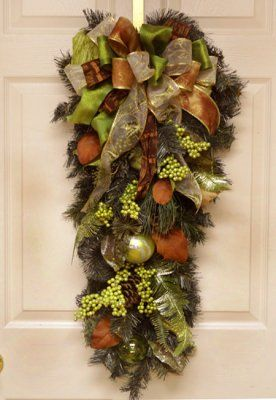 "Green and Brown Ornament Holiday Door Swag CR4582 - Display this unique Christmas Door Swag on your door for a diiferent look this holiday season. Created with multiple brown and green ribbons, pine, ornaments, magnolia leaves, and berries. 15"" x 36"" L"