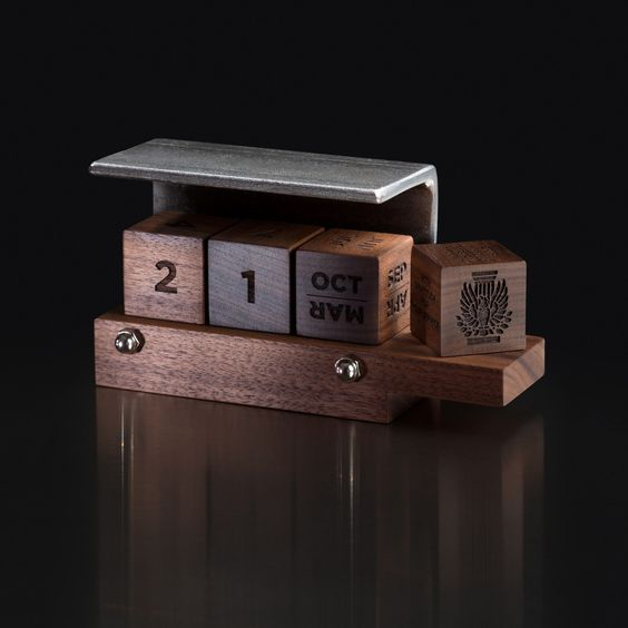 Designed with a steel angle typically found in construction, our perpetual calendar has quickly become a favorite business gift. Three wood cubes perpetually denote days and months and changing them makes for a perfect little daily habit. A fourth cube is added to personalize the piece with your organization's logo and encouraging or congratulatory phrases. Steel & Walnut & Function & Play!