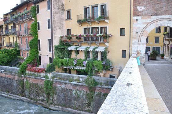 Von der Brücke Ponte Pietra in Verona habt Ihr einen tollen Blick über die Etsch. Am Rande seht Ihr die bunten Außenfassaden der umliegenden Häuser.