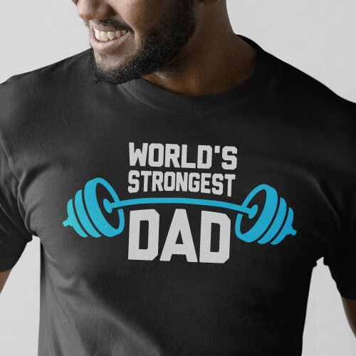 """Perfect for any man who has ever bench pressed a baby, this """"World's Strongest Dad"""" t-shirt takes father's day gifts to the next level. With its simple but heart-felt message this shirt catches the eye and brings a smile as others remember the """"Strongest Dad"""" in their life. Perfect gift for Father's Day!"""