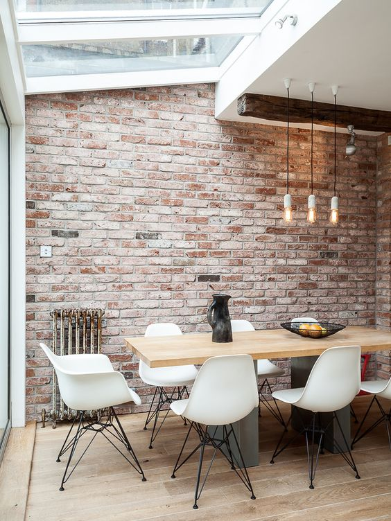 whitewash brick Industrial Dining Room Designs London brick wall distressed wood industrial pendant light natural lighting pendant light reclaimed wood skylight white dining chair whitewashed brick wall wood ceiling beams wood dining table wood floor: