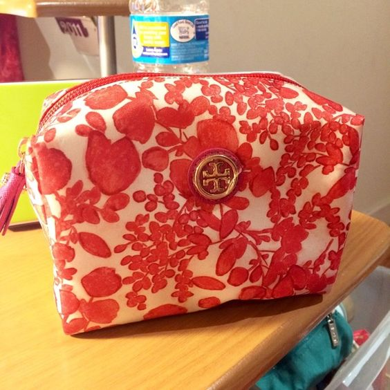 SOLD!! Tory Burch printed nylon cosmetics bag Authentic Tory Burch printed nylon cosmetics bag, red abstract leaf/nature print on ivory ground. Great size pouch to throw into a bigger purse! Inside there is an open side pocket, and the zipper pull has a cute pink tassel. Approximately 6 x 5 x 3 inches. New and never used - plastic covering still on logo! Will include original tag, though it is not attached. Utilitarian, stylish, and cute! Tory Burch Bags Cosmetic Bags & Cases