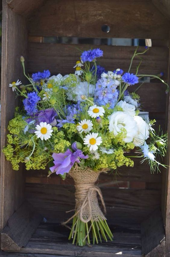 High summer wedding bouquet using cornflowers, lisianthus, alchemilla mollis, camomile, love-in-a- mist, delphinium, and sweet peas bound with string. Just picked, rustic wedding flowers. Wild & Wondrous Flowers: