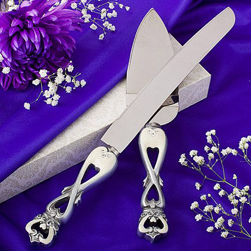 """Each crown design 12"""" x 1"""" cake knife and 10"""" x 2"""" server, has a pewter-colored, cut out poly resin crown design handle with rhinestone accents. engraved at no extra cost."""