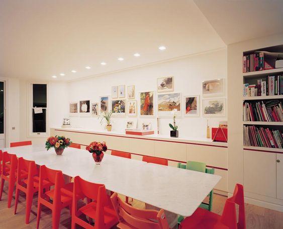 Focolare domestico La sala da pranzo, che si intuisce essere il centro della vita famigliare con i numerosi giochi da tavolo e le tante sedute, comprese quelle per i bambini più piccoli. Il lungo tavolo e le sedie rosse sono pezzi firmati Barber Osgerby