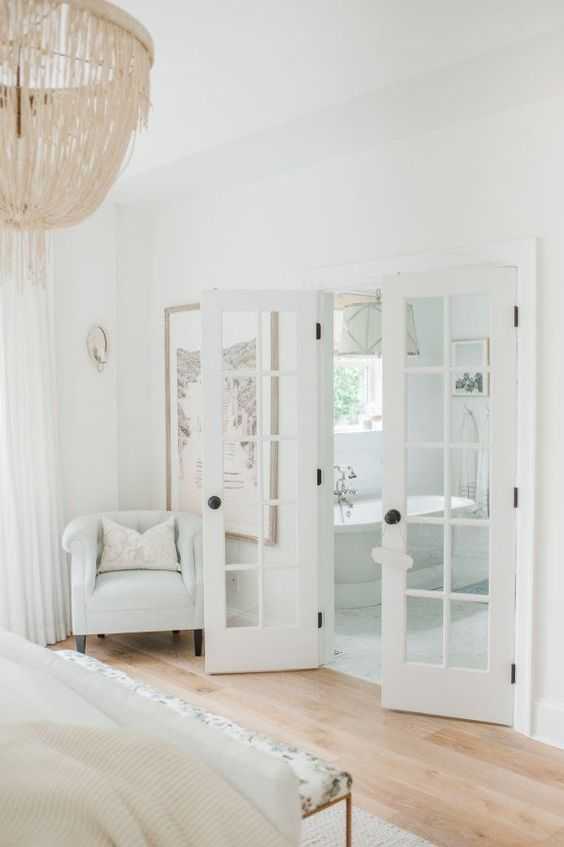 White Master Bedroom suite with French doors that open to master bathroom