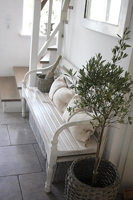 Welcome home... what a pretty foyer!  An old wooden garden bench, some cosy cushions and a small green plant